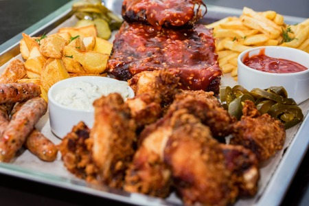 Dish of mixed meats. Grilled ribs, chicken wings and sausages with French fries