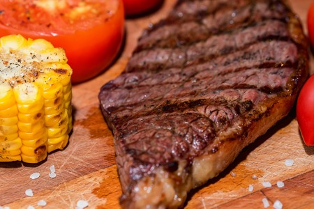 Close up freshly grilled steak on wood with tomatoes and corn Stock Photo