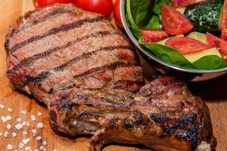 Close up freshly grilled bone steak on wood and fresh salad in bowl