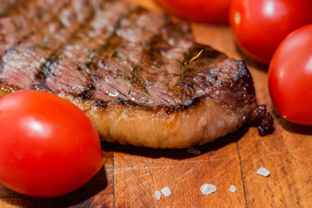 Close up freshly grilled steak on wood with tomatoes