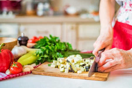 Female hand with knife cuts eggplant on board in kitchen. Cooking vegetables
