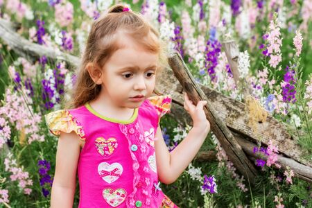 Cute sad baby girl in bright dress looks down outdoors in green field