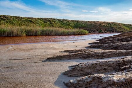 View of small red water river full of iron in beautiful steppe Imagens