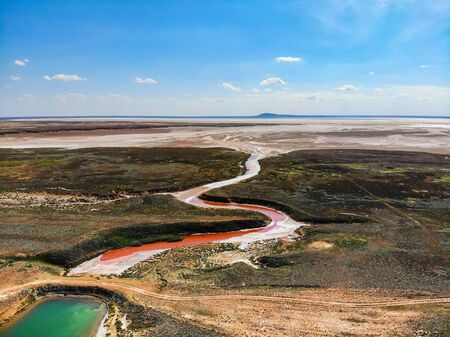 Amazing aerial view of small red water river and green water lake in Baskunchak Imagens