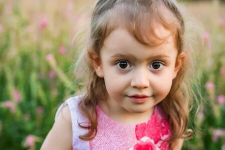 Cute thoughtful baby girl outdoors in green field. Child portrait