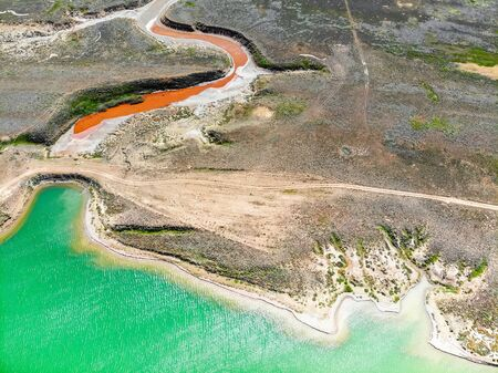 Amazing aerial view of small red water river and green water lake Baskunchak Imagens