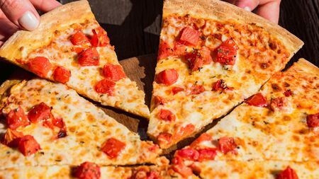 Peoples hands taking slices of fresh pizza Margherita with tomatoes