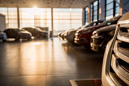 New cars at sunlit dealer showroom close view Archivio Fotografico