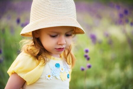 Cute serious baby girl in hat looks down outdoors in green field. Child portrait