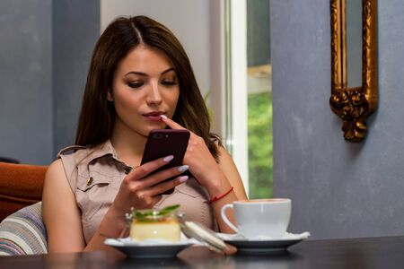 Beautiful thoughtful woman using a mobile phone in cafe. Reading news or SMS