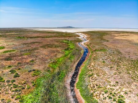 Amazing aerial view of small red water river leading to Baskunchak