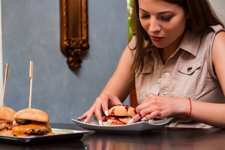 Young woman eating hamburger in restaurant with red sauce on her hand
