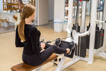 Back view young woman does lat exercises on gym machine