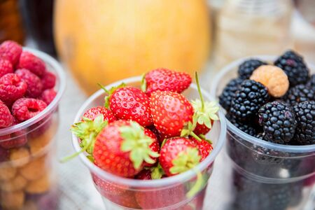 Fresh berries in plastic glasses for sale in market Stok Fotoğraf