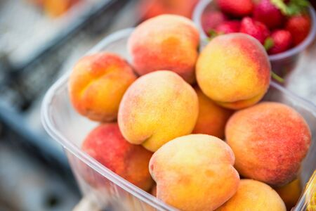 Close view fresh delicious peaches in plastic container for sale in local market. Organic summer vegetarian food
