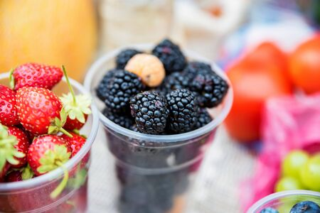 Close view of several plastic glasses full of fresh organic strawberry and blackberry on local market. Organic summer vegetarian food Stok Fotoğraf