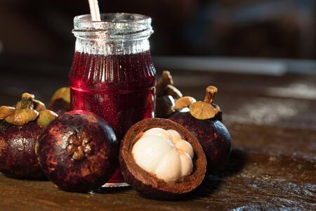 Fresh Mangosteen fruit and drink in jar on wooden background Stockfoto - 129111510