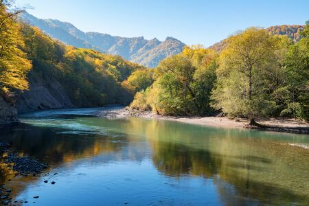 Peaceful autumn landscape with wide mountain river and forest Stockfoto - 129111516