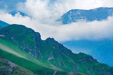 Scenic view of foggy mountains. Clouds and green mountain forest view