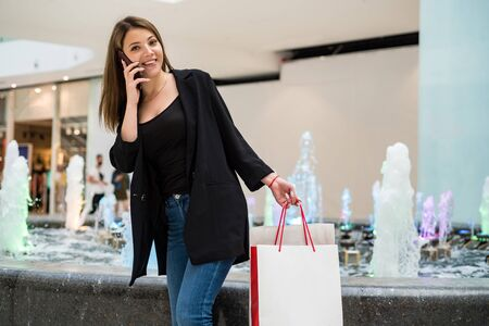 Beautiful brown-haired girl with shopping bags uses phone in mall Фото со стока