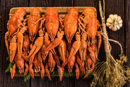 Boiled crayfish on rustic wooden background top view