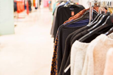 Sweaters hang on rails in modern clothes shop