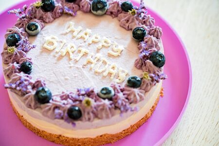Close up birthday cake with cream and blueberries