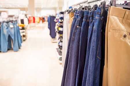 Trousers hang on rails in modern clothes shop