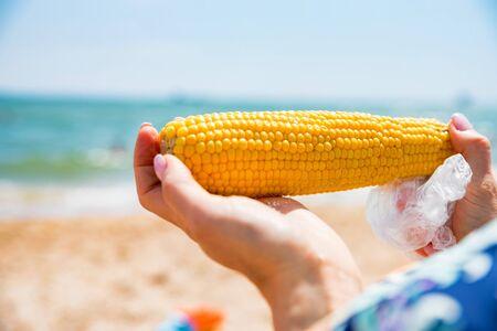 Hands hold boiled corn on sunny beach Фото со стока - 131994860
