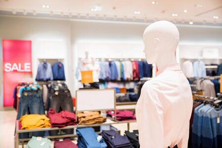 White mannequin in clothes shop with blurred interior background Фото со стока