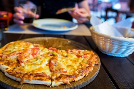 Delicious fresh pizza with tomatoes, salami and melted cheese close Фото со стока