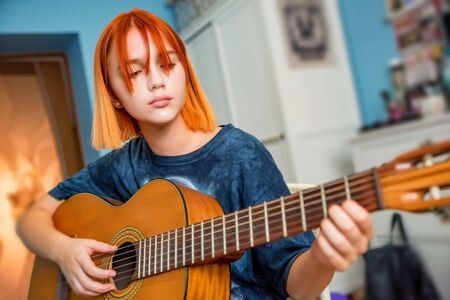 Pretty red-haired teenage girl plays guitar in her room Фото со стока - 131065425