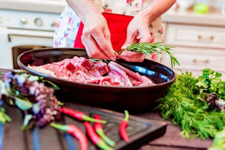 Cook adds rosemary to raw lamb ribs on frying pan close up