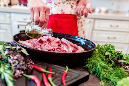 Cook adds oil to raw lamb ribs on frying pan close up