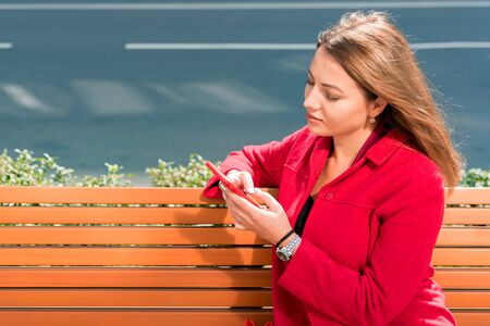 Beautiful young woman in red coat uses smartphone while sitting on bench