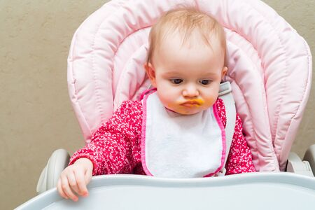Small baby girl in pram with dirty mouth while feeding Stock Photo