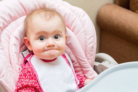 Funny baby girl while being fed in her pram
