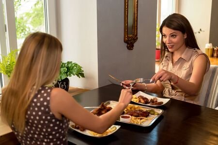 Two girl friends have lunch in modern restaurant