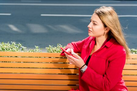 Beautiful young woman in red coat uses smartphone while sitting on bench Фото со стока - 130636376