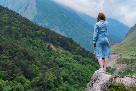 Female hiker takes photo of beautiful mountains while standing on rock Фото со стока - 130636448