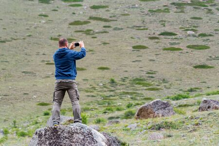 Male hiker takes photo of beautiful mountains while standing on rock Фото со стока - 130636450