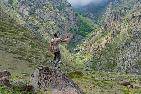 Male hiker takes photo of beautiful mountains while standing on rock Фото со стока