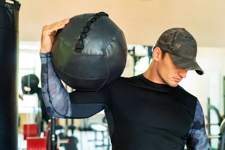 Athlete is holding black exercise ball in gym Фото со стока