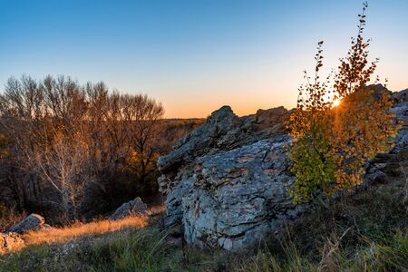 Picturesque steppe landscape with rocks, fall trees and clear sky before sunset