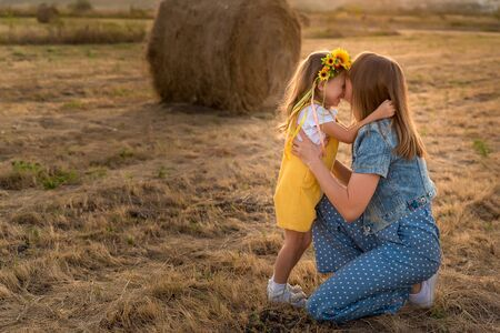 View of happy little girl hugging her young mother in sunlit field in fall. Happy childhood concept