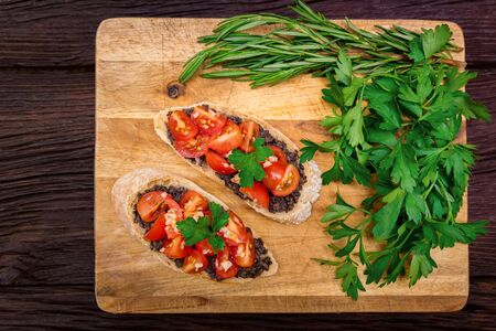 Studio picture of delicious Italian bruschetta with truffle pate on wooden board. Healthy breakfast concept Фото со стока - 132462600