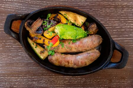 Top view home-made grilled pork sausages with vegetables on frying pan