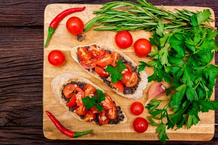 Studio picture of delicious Italian bruschetta with truffle pate on wooden board. Healthy breakfast concept