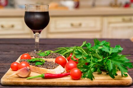 Fresh tasty bruschetta with truffle sauce, vegetables and red wine