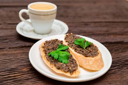 Studio picture of delicious Italian bruschetta with truffle pate on wooden board. and cup of coffee. Healthy breakfast concept